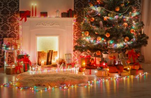 Christmas living room decorations. Beautiful xmas lights garland, decorated christmas tree near fireplace. Modern interior design, magic atmosphere. Winter holidays night, candles and present boxes