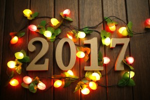 2017 Happy New Year, wooden figures and flashing lights on the retro desktop